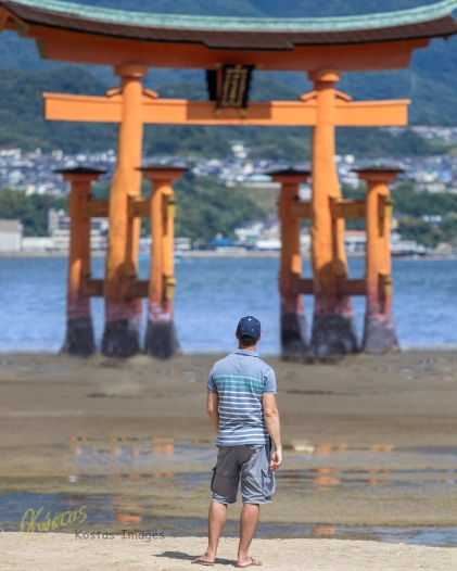 This is me, looking at this magnificent Itsukushima Shrine. The size of this Gate is incredible. The low tide allows for some dry photos in comparison with the high tide which submerges the lower part of the Gate in the water giving the impression that it was actually built on water. Great place for photography. Hiroshima, Japan.