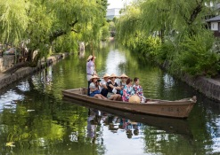 Tourists and yukata girls enjoying a boat ride in the scenic location, Kurashiki Old Town, Japan.