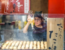 A scene common in Japan, cooking takoyaki at a food kiosk. I have tried it, it's DELICIOUS! Described in wikipedia: Takoyaki is a ball-shaped Japanese snack made of a wheat flour-based batter and cooked in a special moulded pan. It is typically filled with minced or diced octopus, tempura scraps, pickled ginger, and green onion.