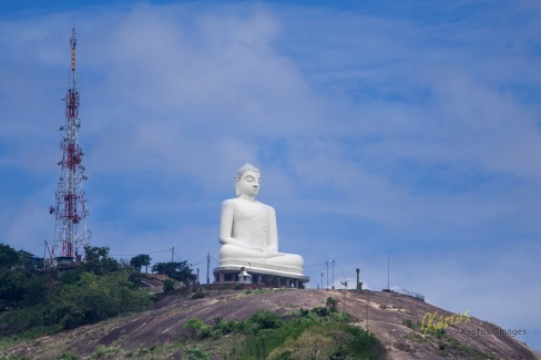 Huge Granite Buddha Statue from Athugala Temple hill, overlooking Kurunegala Town, Sri Lanka. Compare this statue size to the people standing at the base.