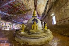 A Stupa with various Buddha statues inside the cave temple, the ceiling is decorated with amazing paintings that keep their colors for a few thousand years...