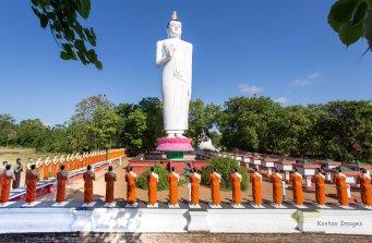 Buddha's disciple statues in front of a huge standing Buddha statue. Sigiriya, Sri Lanka