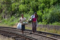 Local ladies crossing the bridge, the train is not passing often, and it's so slow that they can go to the side as soon as they hear it. Nine Arch Bridge, Ella, Sri Lanka.
