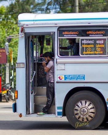 If I had to choose my best street photo, this would be it. A Bus Conductor lighting a cigarette while the bus is under way, the driver is also visible. Galle, Sri Lanka.