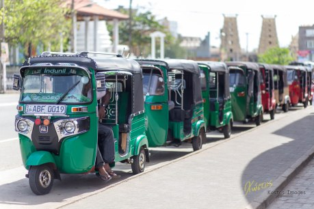 Tricycles and their drivers waiting for passengers outside the Railway Station. They appear of similar built, but in our short stay we have see all shorts of colors and shapes of Tuk Tuks. Galle, Sri Lanka.