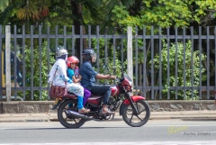 A usual sight in the streets, families (all in helmets) riding motorcycles. The kid was looking at me, although they were under way and I was 50m away from them. Galle, Sri Lanka.