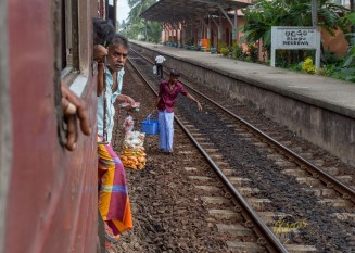 Getting on and off the train at each station (obviously not from the proper platform), these street sellers were having snacks and water. Induruwa, Sri Lanka.