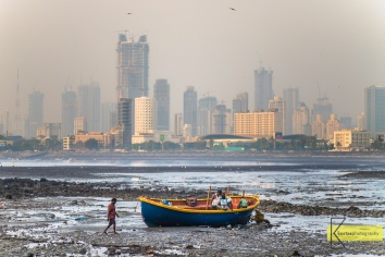 Low Tide is a chance for boat repairs, you can walk to your boat! For me is a chance for an unusual cityscape photo. The foggy afternoon light has added to the atmosphere. Unfortunately high levels of pollution in this congested city. Mumbai, India.