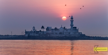 Haji Ali Dargah. Sunset at the famous 600 year old Mosque / tomb. A fine example of Indo-Islamic style of architecture. Left and right on this thin piece of land you can spot the numerous visitors of the Mosque. Got lucky with the sun, the following day the visibility was poor. Mumbai, India.