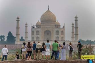 A group of tourists admiring the view of Taj Mahal, from Mehtab Bagh garden. Agra, India.