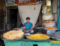 A seller in front of huge pile of dosa, street food in Srinagar, Kashmir, India