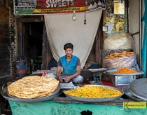 A seller in front of huge pile of dosa, street food in Srinagar, Kashmir, India