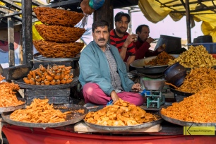 Seller surrounded by his fried street food, Srinagar, Kashmir