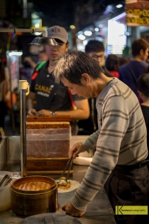A street vendor carefully preparing Taiwan's ice cream burrito. A local delicacy of fresh peanut bar served with ice cream and coriander. Very tasty! Shilin Night Market, famous for the tasty street food.