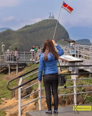 Tour Guide signaling her group in Yehliu Geopark, Taiwan.