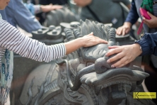 Visitors touching the Lion Statue for good luck outside Dragon and Tiger Pagodas in Kaohsiung.
