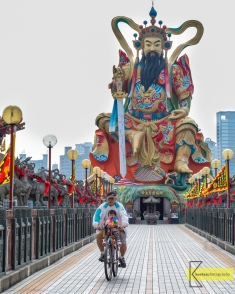 Taking his grandchild or child for a bike ride is common, but in front of this background, (the Great Warrior Statue 玄天上帝神像) makes it unique! Kaohsiung, Taiwan.